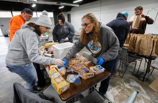 Gathering Friends volunteers Catrin Scott, left, Alan Reed, top left, Autumn Moffatt, center back, and Tami Reed, center front, make up sandwiches to hand out to the homeless at the Connecting Grounds on Tuesday, March 17, 2020.