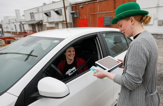 Caitlin Johnson swipes a credit card after delivering a six-pack of Cobra Scare to Megan and Chris Blake at Mother's Brewing Company on Tuesday, March 17, 2020. Mother's, along with other breweries and restaurants in Springfield, are moving to carry-out and delivery only in response to the COVID-19 virus.