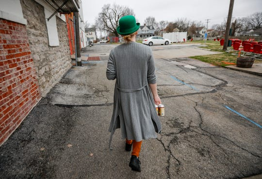Caitlin Johnson carries a six-pack of Cobra Scare out to a drive-thru customer at Mother's Brewing Company on Tuesday. Mother's, along with other breweries and restaurants in Springfield, is moving to carry-out and delivery only in response to the COVID-19 virus.