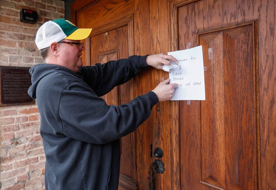 Scott Morris, owner of Falstaff's, posts a sign on his door on Wednesday, March 18, 2020, letting people know there is no food, cash, or alcohol inside as his business closes due to the coronavirus.