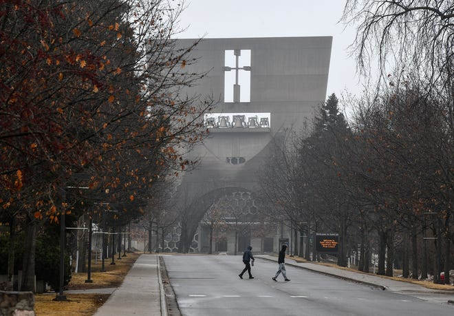 People cross the road near the St. John's Abbey Church on a mostly-deserted campus Wednesday, March 18, 2020, at St. John's University in Collegeville.