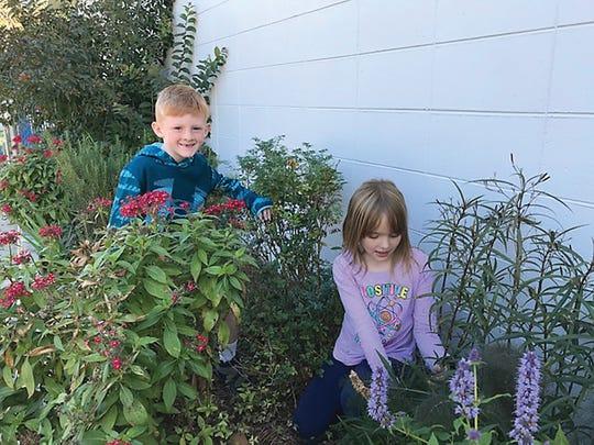 Maya Mistich and Brayden Thomas help in the garden at Gilchrist.