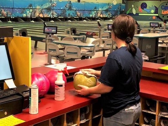 Staff members at Capital Lanes on Capital Circle sanitize bowling balls at the checkout counter following every session to offset the spread of the coronavirus.
