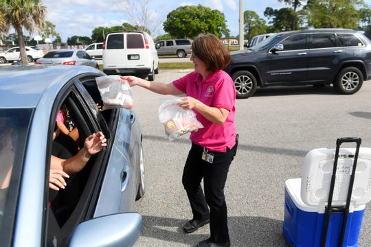 Mellisa Toperzer, a Food and Nutrition Services field manager with the Indian River County School District, hands out lunches to students who are waiting with parents in line to receive a laptop from the district on Wednesday, March 18, 2020, at Vero Beach Elementary School in Vero Beach. The district is issuing laptops to students to ensure they are connected to teachers and assignments during school closures due to the coronavirus. Vero Beach Elementary School is one of six locations across the districts were parents can pick up a laptop for their students.