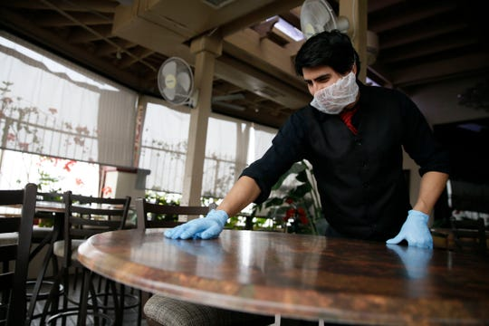 Roberto Echavarria Henric cleans tables at Mesa Street Grill on Tuesday, March 17, in El Paso. Echavarria Henric was cleaning the restaurant since the dining room was closed and the restaurant shifted to curbside pickup and delivery.