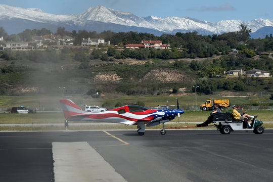 A plane gets towed from the runway at Camarillo Airport on Wednesday after a crash.