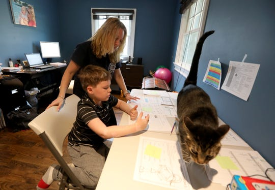 Gilian Goldman-Klein helps her son Ethan,6, with his math work as he does his school work at their Bedford, N.Y. home March 18, 2020. Ethan is a first-grader at the Bedford Village Elementary School. Students of all ages have started schooling at home as schools have closed due to coronavirus concerns.