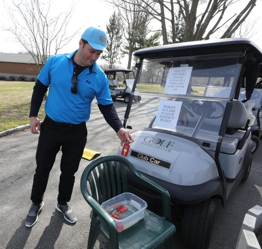 Tom Bopp from New Rochelle, drops his golf cart key into a sanitizing solution after his round at the Saxon Woods Golf Course in Scarsdale, March 18, 2020.