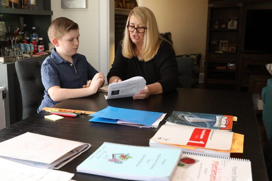 Suzanne Tecza, a library specialist at a local school, works with her son Gavin, a fourth-grader at Chatsworth Avenue Elementary School, on his ELA assignment at their home in Larchmont March 18, 2020. Tecza has set up a schedule to homeschool her son at home during their self-quarantine.