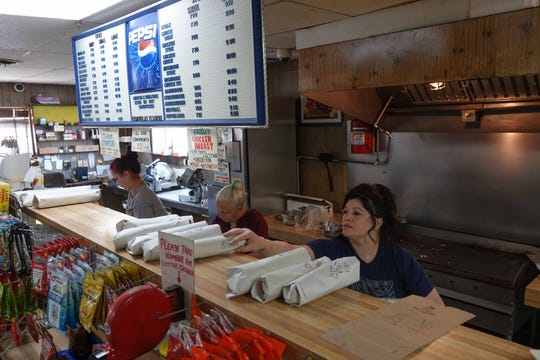 Employees pack up takeout subs at Casapulla's in Elsmere, on Wednesday afternoon. Third generation owners Lou and Annlyn Casapulla have seen about a 20 percent increase in business since restaurants have been restricted to takeout only.