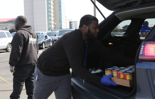 A Food Bank of Delaware worker put food in the back of a car Wednesday morning.  The organization held a food giveaway, but had to turn away vehicles due to not having enough food and traffic issues around the Wilmington Riverfront.