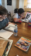 James and Ja'nya, 10 and 12, work at the kitchen table during their homeschool stint as schools shut down in an attempt to flatten the curve of coronavirus spread.