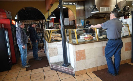 Customers wait for takeout orders to be prepared at Little Vinnie's in Chestnut Run Shopping Center on Wednesday afternoon.