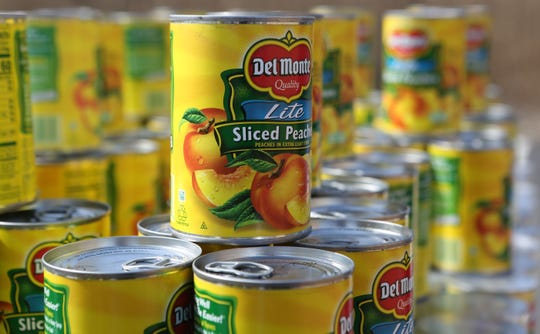 Cans of sliced peaches stacked on pallets at the Food Bank of Delaware's food giveaway Wednesday morning.