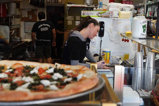 Tina Decker, a counter helper at Little Vinnie's Pizza and Pasta in Chestnut Run Shopping Center, receives a takeout order over the phone on Wednesday. Little Vinnie's is trying to see how takeout business will go after the coronavirus outbreak caused the state to shut down all sit-down dining.