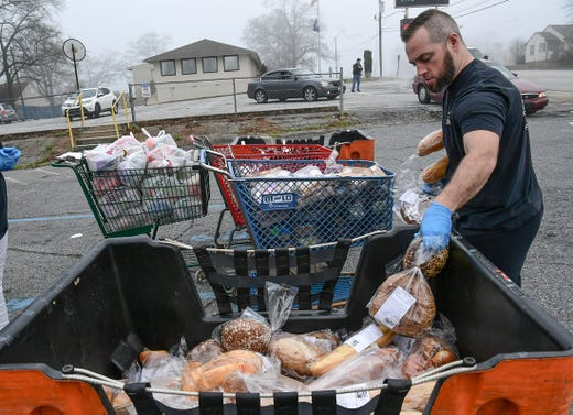 Jordan Cook of Anderson Interfaith Ministries Hunger Ministries, gets ready to load a car in the drive-through during food pantry hours in Anderson, S.C., March 18, 2020.