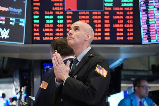 Traders work on the floor at the opening bell of the Dow Industrial Average at the New York Stock Exchange on March 18, 2020 in New York.