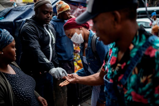 A man sprays commuters with hand sanitizer as a preventive measures in Johannesburg, South Africa on March 18, 2020.  African countries have been among the last to be hit by the global COVID-19 coronavirus epidemic but as cases rise, many nations are now taking strict measures to block the deadly illness.
