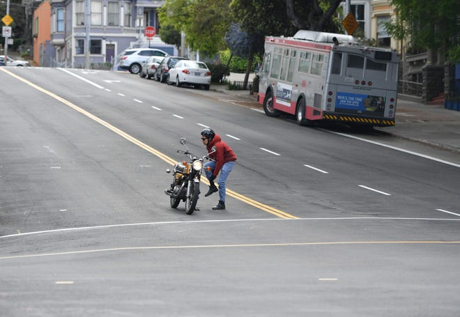 A motorcyclist adjusts his pants from the middle of an empty street in the Haight Ashbury area of San Francisco, California on Tuesday. Millions of San Francisco area residents were ordered on Monday to stay home to slow the spread of the deadly coronavirus as part of a lockdown effort covering a section of California including Silicon Valley.