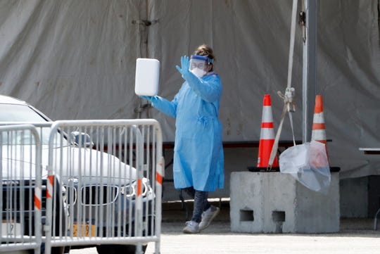 A medical worker signals as she emerges from a tent at a New York State Department of Health COVID-19 testing site at Jones Beach State Park on Long Island, Wednesday, March 18, 2020, in Wantaugh, N.Y.  For most people, the new coronavirus causes only mild or moderate symptoms. For some it can cause more severe illness. (AP Photo/Kathy Willens) ORG XMIT: NYKW101