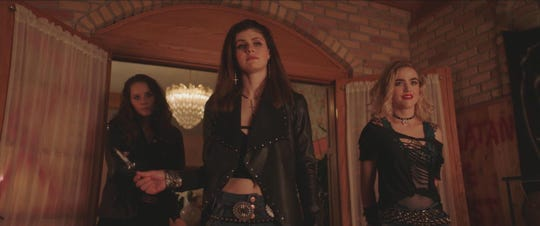 """Alexis (Alexandra Daddario, center) and her pals (Amy Forsyth and Maddie Hasson) pick up some dudes at a local heavy-metal show in the horror comedy """"We Summon the Darkness."""""""