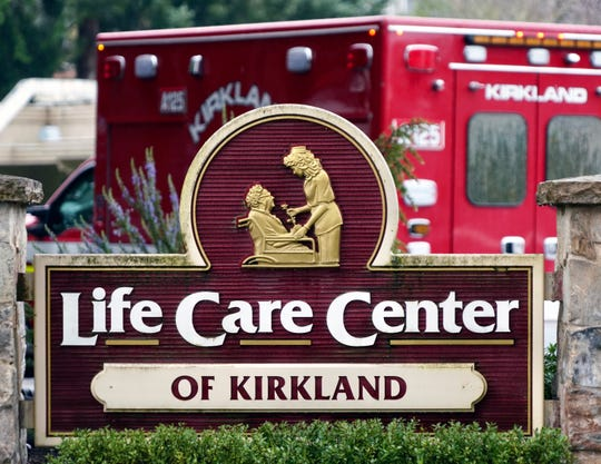 An ambulance waits outside the Life Care Center of Kirkland, Washington, during the coronavirus outbreak.