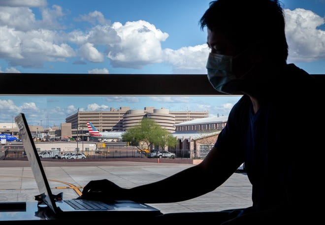 A passenger uses his computer while wearing a protective face mask at the Phoenix International Airport on March 14.