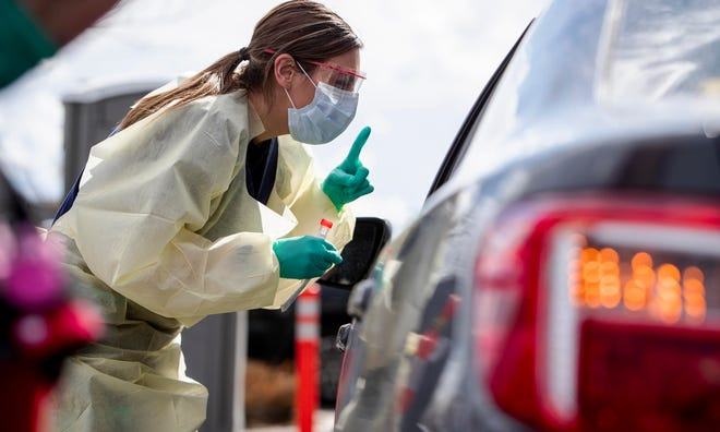Ashley Layton at St. Luke's Meridian Medical Center takes a swab sample at an outdoor drive-thru screening station for COVID-19 in Meridian, Idaho, on March 17.