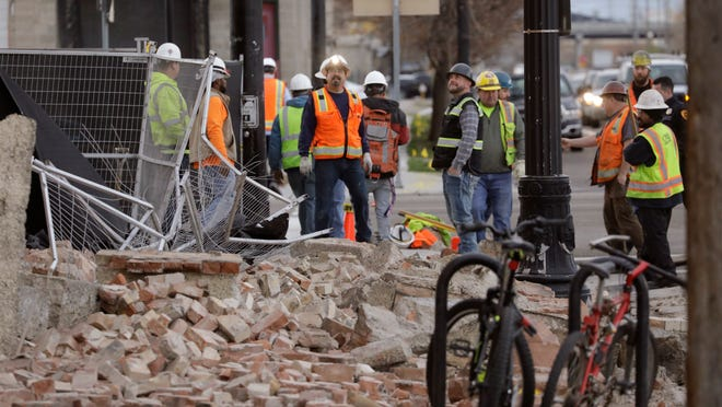 Construction workers look at the rubble from a building after an earthquake March 18, 2020, in Salt Lake City.