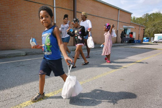 Kenny Scott, 4 walks with his mother Kayla Hutchinson and sisters after they picked up their grab-and-go lunch and snack at Carter G. Woodson Elementary School in Jacksonville, Fla. on MArch 17, 2020. Duval County Schools started handing out grab-and-go lunches and snacks at neighborhood schools around the city , March 17, 2020 to continue the meals that students would have been getting had school been in session.