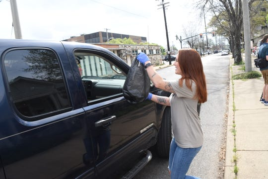 Shana Prince Lazarone plays car hop and takes a meal to a waiting car outside Word of Mouth Cafe. John Foster Gunter, owner of Word of Mouth Cafe in downtown Alexandria, and his sons Clark Gunter and Hardy Gunter prepared free plate lunches for the elderly Thursday from their cafe.