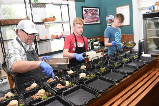John Foster Gunter, owner of Word of Mouth Cafe in downtown Alexandria, and his sons Hardy Gunter and Clark Gunter prepare free plate lunches for the elderly Thursday from their cafe.