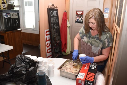 Duana Juneau prepares bread pudding for free plate lunches John Foster Gunter, owner of Word of Mouth Cafe in downtown Alexandria, and his sons Clark Gunter and Hardy Gunter were offering for the elderly Thursday.