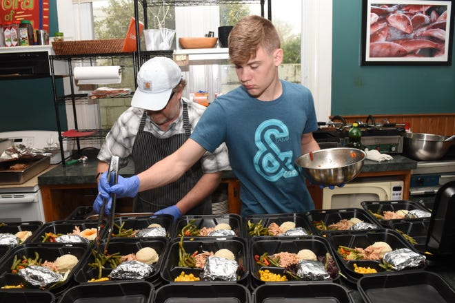 This photo appeared on Time.com recently in a piece highlighting how everyday people around the world are helping those in need during the coronavirus crisis. John Gunter (left), owner of Word of Mouth Cafe,  and his sons prepared plate lunches for local elderly people.