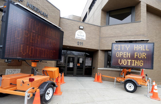 Emergency signs inform visitors that Neenah City Hall is open for early voting but otherwise is closed to the public because of the COVID-19 pandemic.