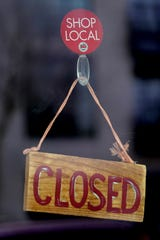 A closed sign hangs on the front door of a restaurant  in downtown Appleton on Thursday.