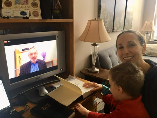 Laurie Quinland, with her son, Bruce, takes part in a livestreamed service from Holy Trinity Episcopal Church in South River. The Rev. Gregory Bezilla, rector, is on screen.