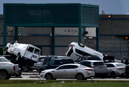 A van and an SUV are stacked atop other vehicles in the parking lot of the French Robertson Unit outside of Abilene Thursday. Heavy winds from an early morning storm wreaked havoc from Tye to the prison, destroying buildings and killing livestock.