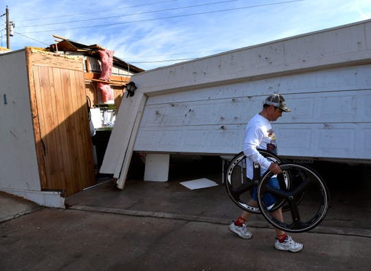 """William """"J.R."""" Brock carries a pair of bicycle tires out of his toppled garage Thursday. A tornado damaged his Tye home early that morning, but not before he and his family made it to their storm shelter."""