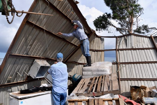 Marshal Mepps stands atop a pallet of supplies inside the remains of Randall Franke's workshop Thursday. Danny Lewis, Franke's brother-in-law, watches.