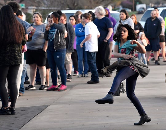 Leana Lopez, 8 and a third-grade student at Lee Elementary, passes the time with some high-flying kicks as her family waits in line at Johnston Elementary School on Thursday. About 250 people were waiting in line before 7 a.m. to receive laptops from the Abilene Independent School District. Those will be used to facilitate educational activities while students are out of school due to the coronavirus.
