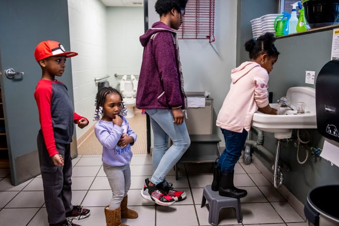 Titus Perry, 6, Aniyah Taylor, 3, Andrea Taylor and Khilee Kirk, 4, wash their hands before breakfast on Thursday, March 19, 2020 at the YMCA Battle Creek, Mich.
