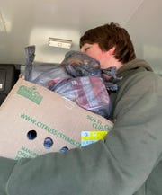 Andrew Mauney, a freshman at Battle Creek Central, helps deliver meals to students at Battle Creek Montessori Academy
