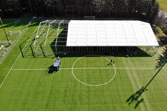 In this aerial drone photo, workers erect a temporary field hospital for use by people unable to isolate and recover from COVID-19 in their own homes on a soccer field Thursday, March 19, 2020, in the Seattle suburb of Shoreline.