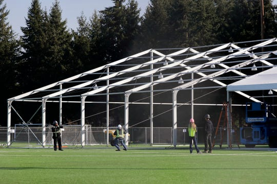 Workers erect a temporary field hospital for use by people unable to isolate and recover from COVID-19 in their own homes on a soccer field Thursday, March 19, 2020, in the Seattle suburb of Shoreline.
