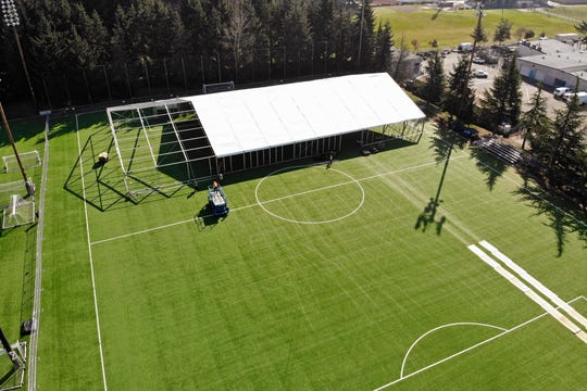 "In this aerial drone photo, workers erect a temporary field hospital for use by people unable to isolate and recover from COVID-19 in their own homes on a soccer field Thursday, March 19, 2020, in the Seattle suburb of Shoreline. The field hospital will provide up to 200 beds, according to a city website, and will house ""people exposed to, at risk of exposure, or becoming ill with the novel coronavirus."""