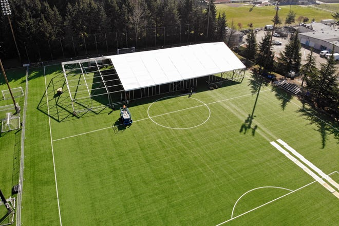 """In this aerial drone photo, workers erect a temporary field hospital for use by people unable to isolate and recover from COVID-19 in their own homes on a soccer field Thursday, March 19, 2020, in the Seattle suburb of Shoreline. The field hospital will provide up to 200 beds, according to a city website, and will house """"people exposed to, at risk of exposure, or becoming ill with the novel coronavirus."""""""