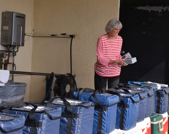 Meals on Wheels volunteer coordinator Melissa John puts out boxes of gloves and safety instructions for the volunteer drivers. Meals on Wheels, administered locally by Aging Matters in Brevard, is still delivering meals, but with stricter guidelines due to coronavirus concerns. Drivers have gloves and additional safety instructions.