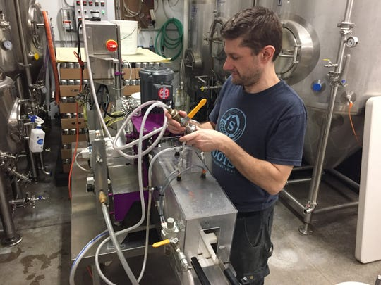 Brewer/co-owner Dan Ukolowicz works on the canning machine at Simple Roots Brewing in Burlington on March 19, 2020.
