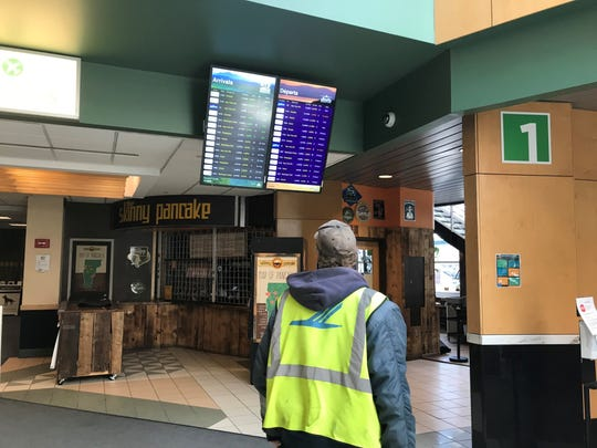 An airport worker checks the arrival and departure screen at Burlington International Airport on Wednesday, March 18, 2020.
